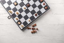 Game Board With Chess Pieces On White Wooden Table