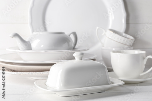 Foto Set of clean dishware on white table