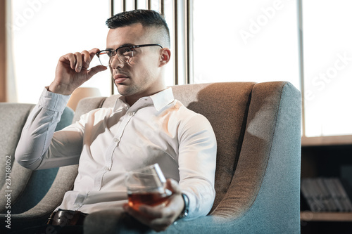 Fotografie, Tablou  Young dark-haired businessman feeling rested while drinking whisky