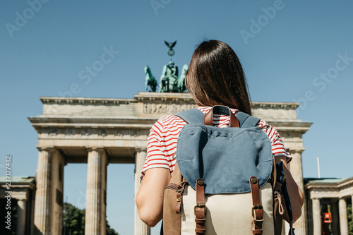 Foto  A tourist or a student with a backpack near the Brandenburg Gate in Berlin in Germany, looks at the sights