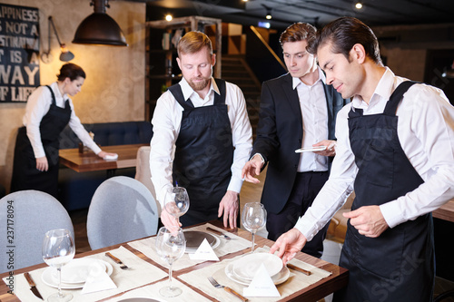 Serious restaurant manager in formal suit standing at table and explaining setti Fototapete