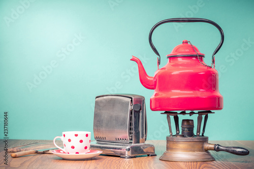 Retro classic red kettle on brass gas stove, a cup of tea, outdated bread toaster, kitchen board and vintage knife on oak wooden table in front mint green background. Old style filtered photo