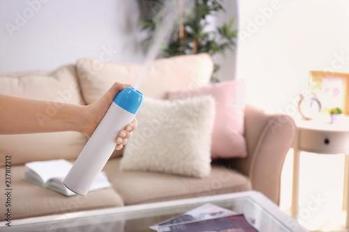 Valokuva  Woman spraying air freshener at home