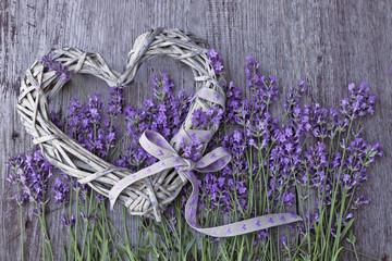 Lawenda kwitnie z łozinowym sercem na drewnianym tle