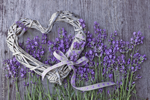 Poster Lavendel Lavender flowers with wicker heart on wooden background