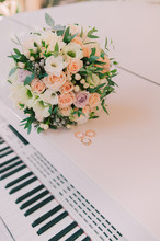 Wedding Rings On The Piano And Flower