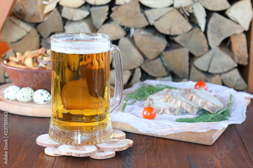 Tuinposter Bier / Cider Mug of light beer and snack on the table against the background of firewood.