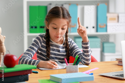 Photo Cute girl with raised index finger doing homework in classroom
