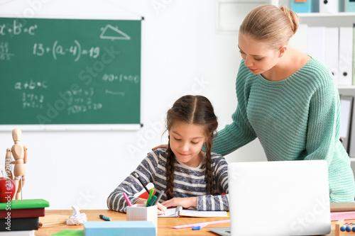 Photo Cute girl with teacher doing homework in classroom