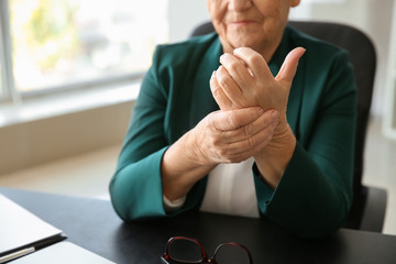 Senior woman suffering from pain in wrist indoors