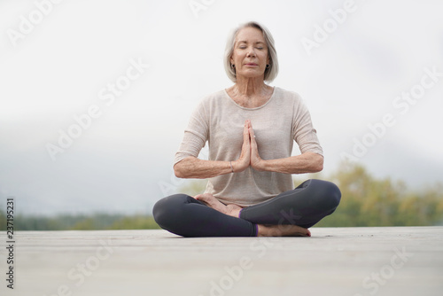 Serene senior woman meditating outdoors