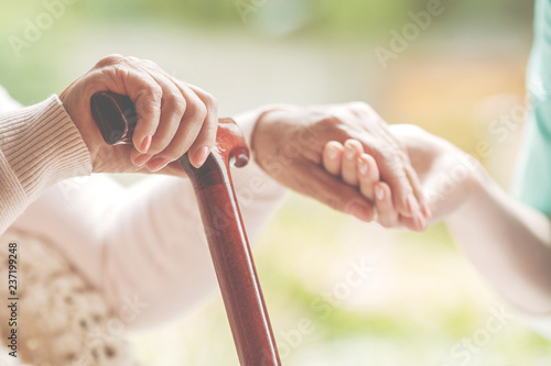 Closeup of senior lady holding walking stick in one hand and holding nurse's han Obraz na płótnie