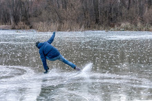Man Falling Down While Ice Skating. Snow Skates From The Scatter In The Parties.