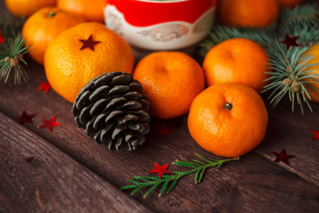 Christmas new year background with tangerines, tea and sweets on the table. winter still. selective focus.