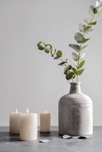 Burning Candles And Vase With Eucalyptus Branches On Grey Table