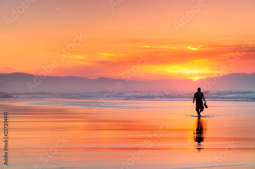 Fotografie, Obraz  lonely person walking on beach at beautiful red sunset