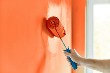 Male Hand Painting Wall With Paint Roller. Painting Apartment, Renovating With Red Orange Color Paint