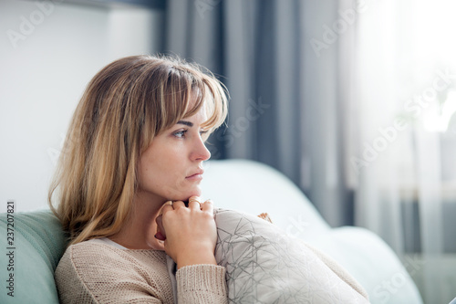 Obraz Depressed woman sitting on sofa at home, thinking about important things - fototapety do salonu