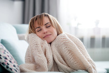 Happy Young Woman Hugging Soft Knitted Sweater, Relaxing On Sofa At Home