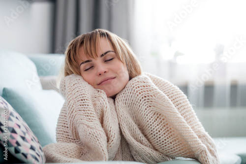 Fotografía  Happy young woman hugging soft knitted sweater, relaxing on sofa at home