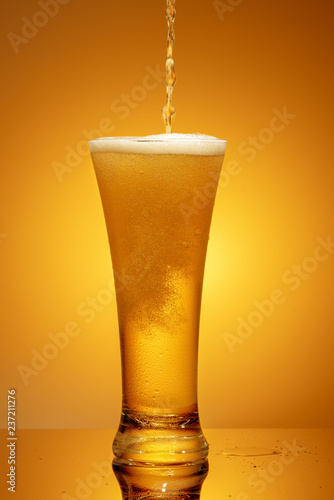 Tuinposter Bier / Cider beer is poured into a glass on a yellow background