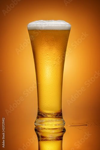 Tuinposter Bier / Cider glass of beer on yellow background with reflection