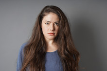 Young Woman With A Serious Look On Her Face - Gray Background With Copy Space