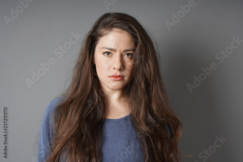 Fotografie, Obraz  young woman with a serious look on her face - gray background with copy space