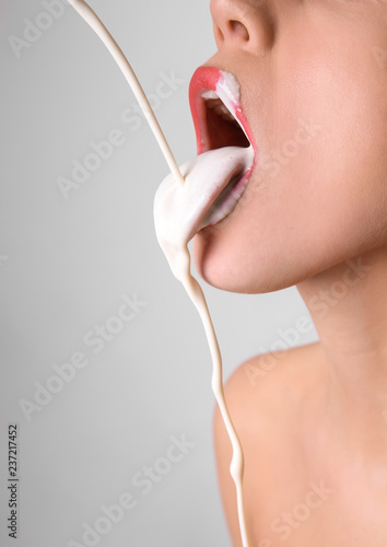 white-liquid-dripping-into-woman-s-mouth-on-light-background-erotic-concept
