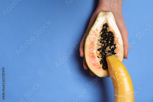 Foto Half of sweet papaya and banana in female hands on color background