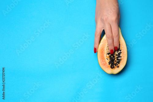 Photo  Female hand and half of fresh papaya on color background