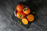 Plate with ripe persimmons on table, top view