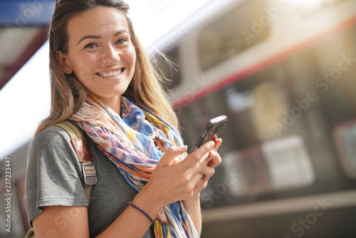 Fotomural Young woman at train station with cellphone