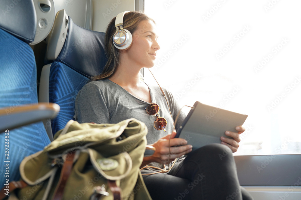 Fototapety, obrazy: Young woman travelling by train with tablet and headphones
