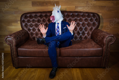 Obraz Funny unicorn in elegant suit siting on sofa like a boss and showing do not bother me gesture. Portrait of unusual man at home. Freaky guy in mask. - fototapety do salonu