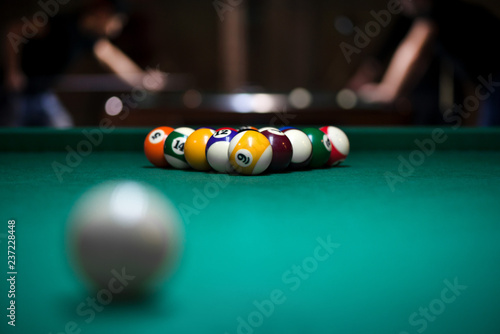 Tela Sport billiard balls set arranged in shape of triangle on green billiard table in pub