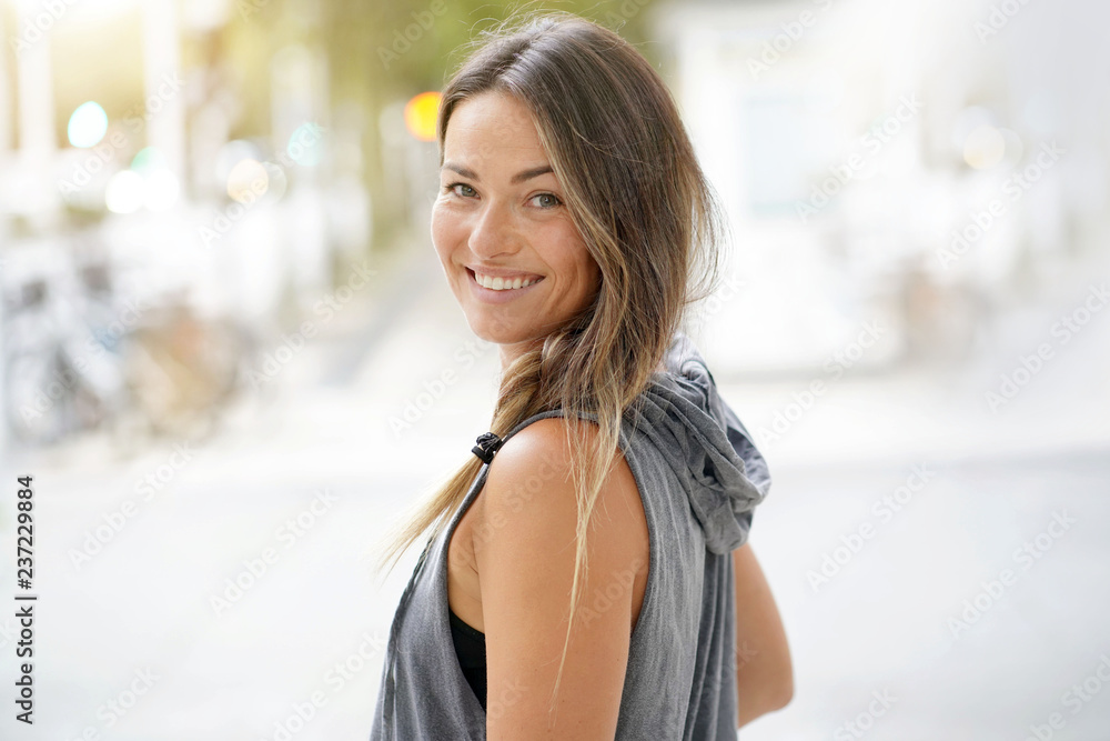 Fototapety, obrazy:  Woman in urbanwear turning around and smiling at the camera
