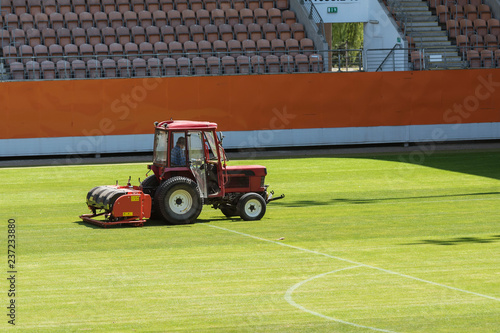 Valokuva Man in tractor aerating a soccer pitch at the stadium.