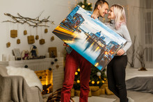 Happy Young Woman Canvas And Her Boyfriend Holding While Moving Into New Home