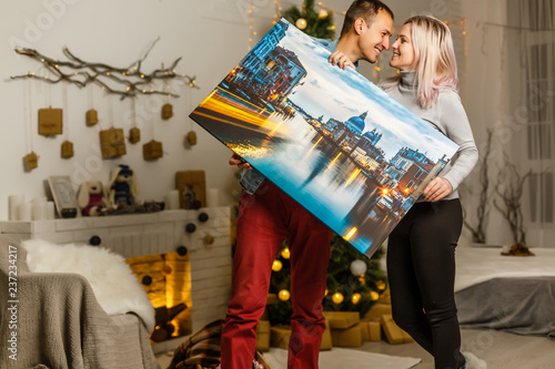 Fotografia, Obraz Happy young woman canvas and her boyfriend holding while moving into new home