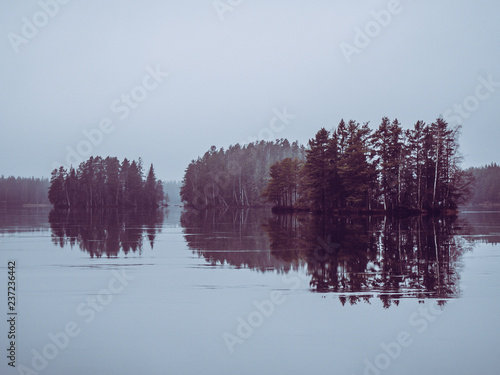 Grey dark and misty lake with small islands in background reflecting like a mirror in the ice. November in Sweden.