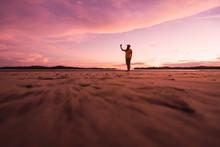Traveler On Sandy Beach In Sunset