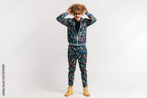 Fotografía  Adult shylish man in fashion clothes, yellow sneakers posing on white studio background