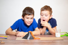 Two Boys Watching A Chemistry Experiment. Volcanic Eruption. School Science Project. Children Surprised. Chemical Reaction Of Baking Soda And Vinegar. Selective Focus
