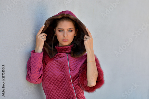 Fotografía  Portrait of a young woman in a red leather jacket in front of a white background