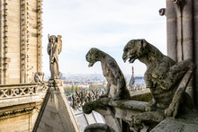 Two Stone Statues Of Chimeras Overlooking The Rooftop Of Notre-Dame De Paris Cathedral From The Towers Gallery With The Statue Of An Angel With Trumpet And The City Vanishing In The Mist.