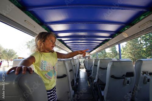 Fotografia  Little blonde little girl in a tourist bus in Athens