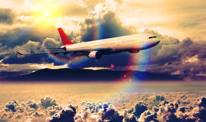 Fototapeta Niebo Concepto de viaje en avión y destino. Avión comercial volando sobre el paisaje del atardecer. Aerolíneas y agencias de viaje