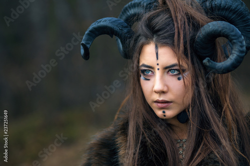 Outdoor portrait of beautiful scandinavian viking woman warrior with blue eyes wearing ram horns Fototapete