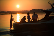 View Of Two Couples In A Boat At Sunset.